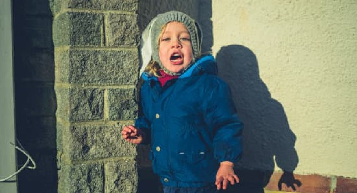 A little toddler is standing in the street screaming at sunset on a winter day